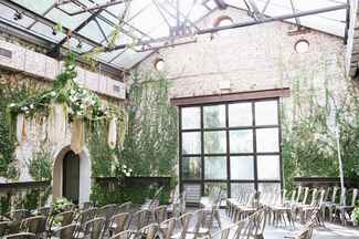 Industrial wedding ceremony space with brick walls and a glass ceiling