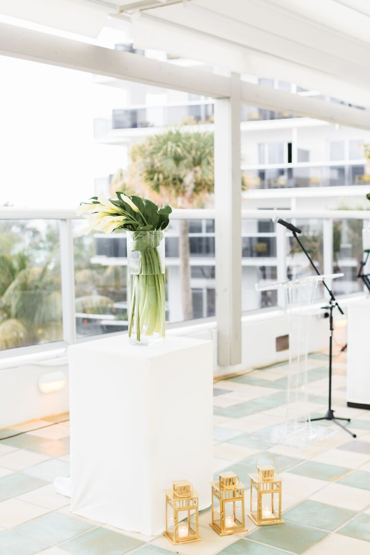 "The ceremony was held on the upper-floor patio of the Confidante in Miami Beach, Florida. ""We wanted the ocean view to be the focal point, so we kept the decor simple and sleek,"" Wes says. ""We went with a white runner down the aisle lined with vintage-inspired gold lanterns. At the altar, we had two large calla lily arrangements."""