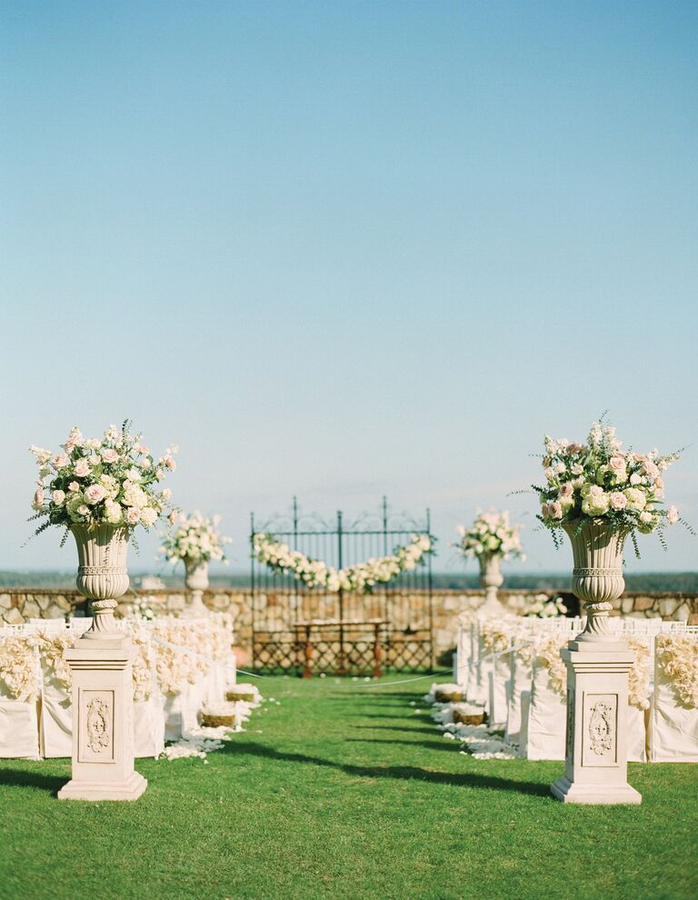 Rose flower arrangements and garlands at outdoor wedding ceremony
