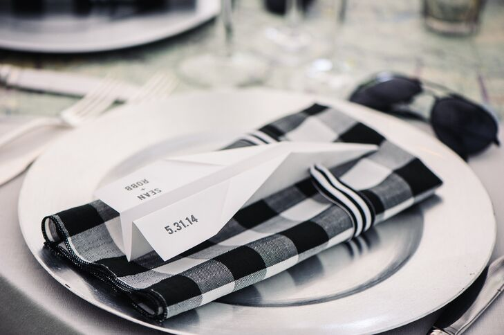 The black and white buffalo check napkins sat on silver chargers with paper plane menus tied with black and white ribbon on top.