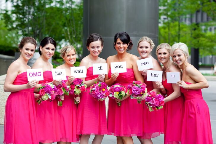 "Teresa's bridesmaids wore matching ""azalea"" pink short strapless dresses by Love Lane that paired perfectly with their bright pink ranunculus bouquets. Teresa gave them custom earrings and bracelets from Erin Gallagher Jewelry and monogrammed necklaces from Mark and Graham. They wrote out a special message, which they photographed and texted to the groom to tease him in anticipation of seeing the bride."