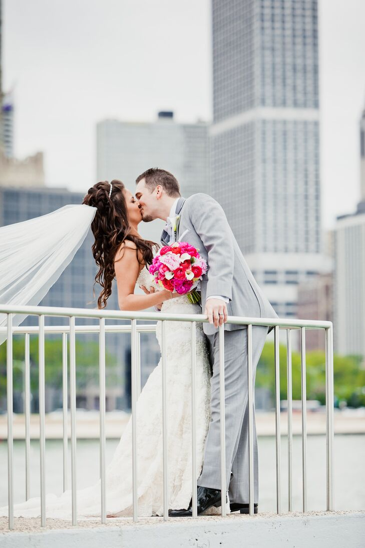 Groom Kisses Bride with Pink Bouquet and Cathedral Veil