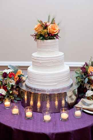 Three tiered white buttercream wedding cake with peach rose and wildflower topper
