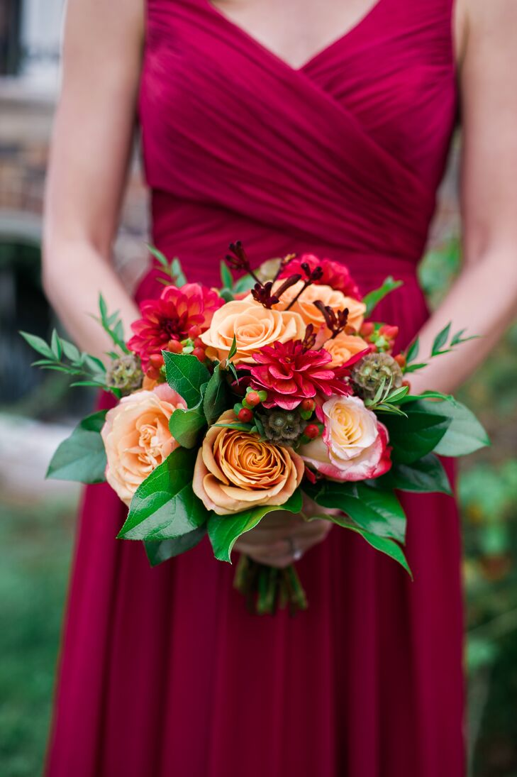 The bridesmaids held bouquets filled with roses and dahlias that resembled Christine's arrangement, but in lighter shades of fall-inspired colors to contrast with their burgundy dresses.