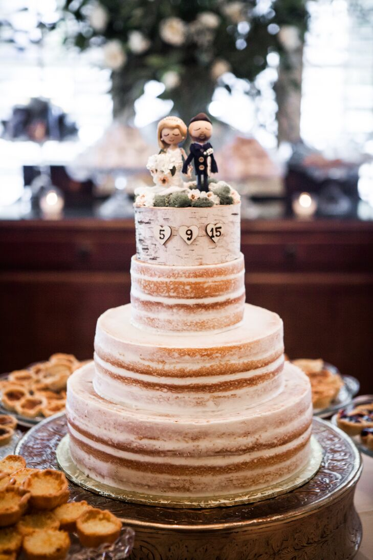 "The couple had a ""naked"" wedding cake, decorated with birch accents and toppers made in their image by the bride's sister."