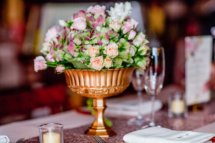 For the centerpieces, Events by Nikki Diaz created classic arrangements of hydrangeas, spray roses, freesias and green amaranthus in gilded vases. To tie the arrangements in with the venue's overall design, the romantic blooms were displayed atop stacks of antique books.
