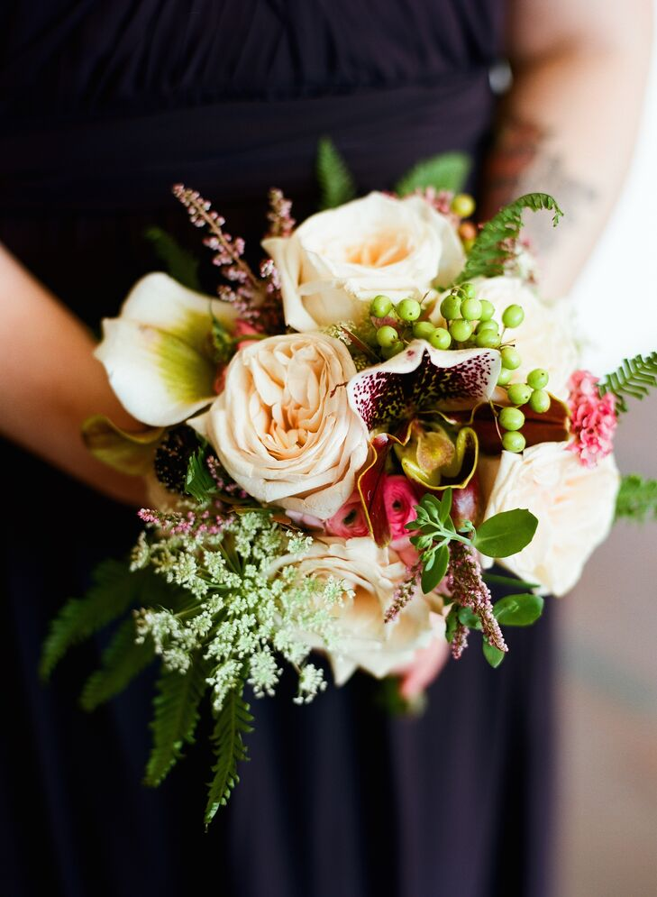 The bridesmaids carried smaller versions of Tessa's bouquet. Martha's Gardens included roses, orchids, Queen Anne's lace, astilbes, ranunculus and hypericum berries in their arrangements for a textured, rustic look.