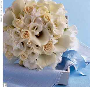White bridal bouquet tied with a blue monogrammed ribbon