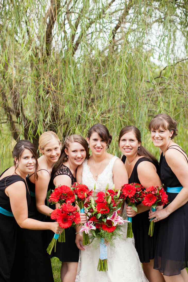The bride posed with her bridal party, who wore black dresses of their choice and held red bouquets of red gerbera daisies and alstroemeria.