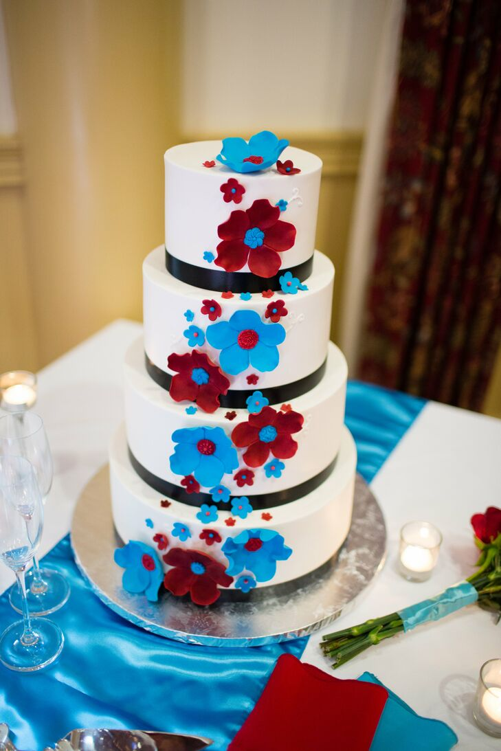 The four-tiered white almond cake had two tiers filled with white chocolate, while the other two were filled with raspberry. The cake was covered in buttercream frosting and accented with teal and red gum paste flowers.