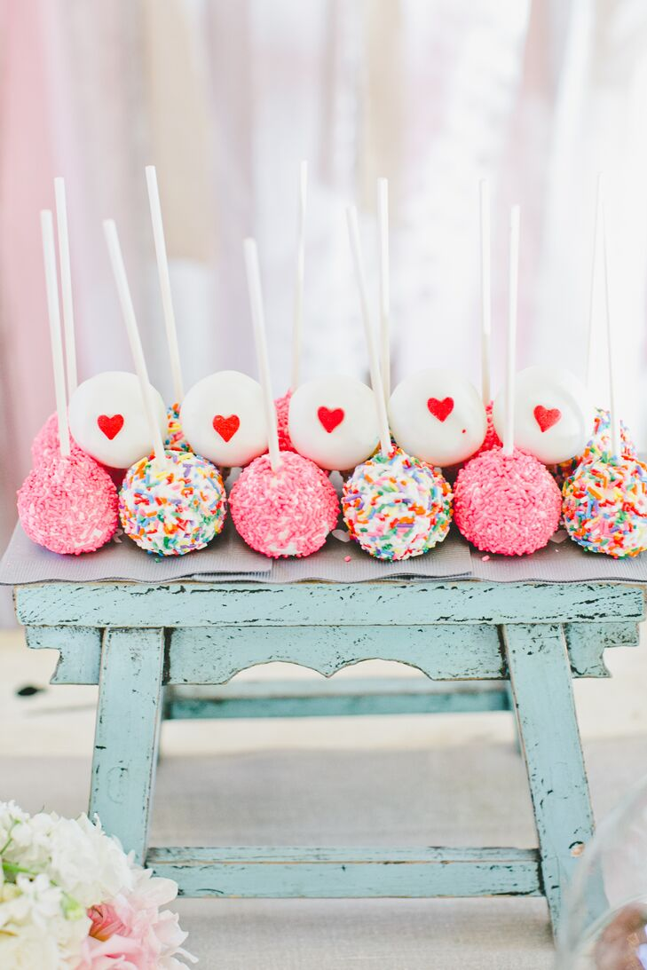 Guests chose from a variety of desserts displayed  together at the reception, including adorable cake pops covered with sprinkles or decorated with heart-shaped designs. They sat on top of a faded blue wooden stand that went along with the rustic vibe.