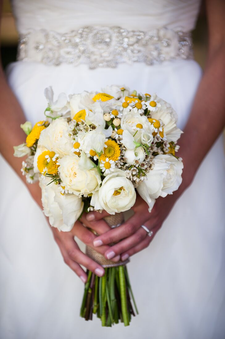 Sarah's bouquet looked as if she had just walked through a field and swept it up on her way to the ceremony. The arrangement of white and yellow blooms looked a little wild and matched her natural wedding theme.