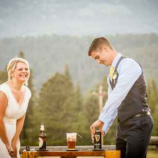 A bride and groom pouring a black and tan drink into a beer glass at their outdoor unity ceremony.