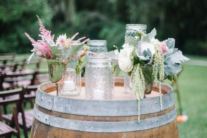 Two large wine barrels stood at the entrance of the ceremony and were decorated with votive candles in textured mason jars and arrangements of pastel florals set in antique vessels.