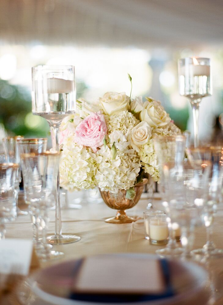 Gold urn centerpieces filled with ivory arrangements