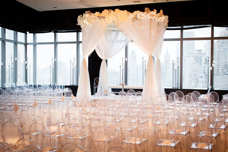 "The Mandarin Oriental's prime location next to Central Park was a major selling point for Allison and Jason. ""Jason and I spend tons of time in Central Park and since it is where he proposed, the venue had special meaning to us,"" says Allison. For the ceremony, the couple went for a modern, ethereal aesthetic, filling the room with clear ghost chairs dotted with paper flowers and a statement chuppah draped in airy white fabric and crowned with large origami flowers."