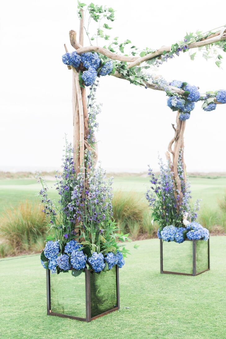 "A driftwood arch draped in hydrangeas, roses, peonies and delphiniums served as the backdrop to Nicole and Joseph's waterfront wedding, while petals adorned the aisle. ""I wanted the overall look to feel warm and relaxed, yet polished,"" Nicole says of their wedding decor."