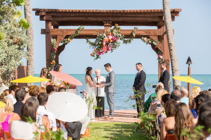 Since the venue already had a standout wedding arbor with intricate carvings on-site, Francesca and Michael highlighted it with just a few accents. A grand garland of eucalyptus, orange lisianthus, pink hydrangeas, bougainvillea and peach roses all wrapped around the front posts.