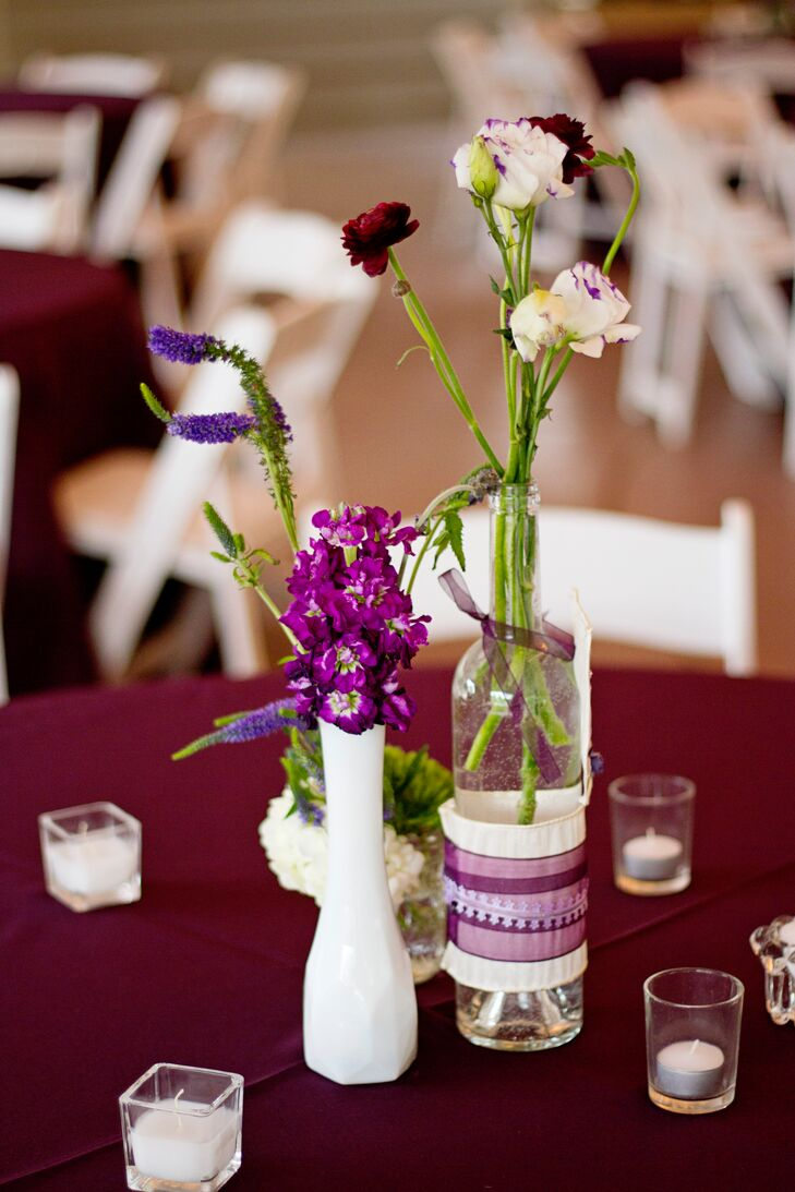 The round reception tables were covered with plum linens and topped with clusters of wine bottles wrapped in raffia and purple ribbon. The bottles held small arrangements of purple calla lilies, lavender, ranunculus and roses.