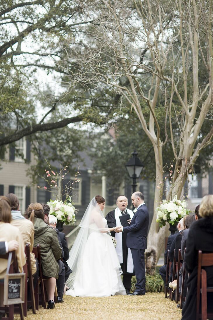 The couple placed dark fruitwood chairs in Washington Square and created an alter space with square wood columns with urns on top filled with white and pink roses, hydrangeas and ranunculus.