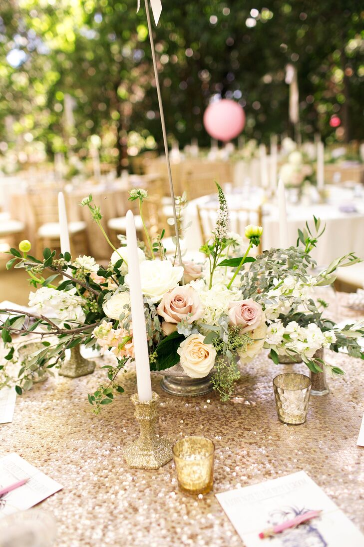 The gold sequin-covered dining tables had overflowing flower centerpieces filled with neutral-colored roses and greenery. The centerpieces were surrounded by votive candles and white tall candlesticks in candelabras, giving the tables a glamorous, elegant look.