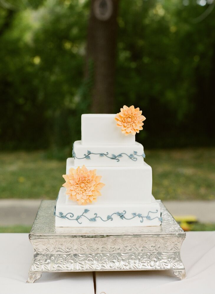 The four-tier ivory cake embodied rustic-chic style through the gray vine patterns that decorated alternating layers. Two sugar flowers shaped like dahlias accented the sides of the dessert.