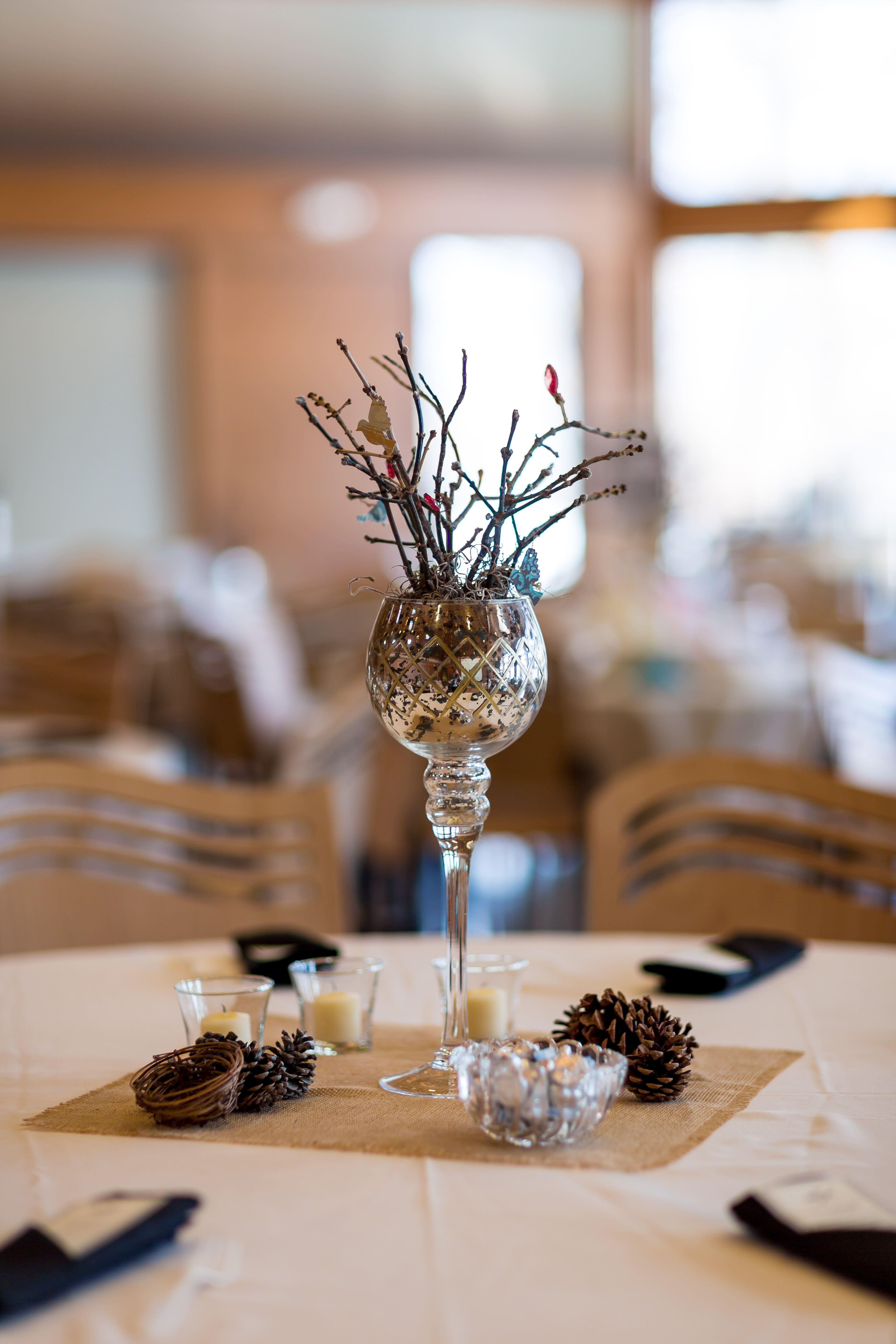 rustic wine glass centerpieces with pinecones and branches