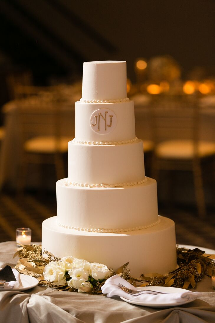 "The wedding cake consisted of five tiers frosted in ivory buttercream with piping separating each tier and the couple's minimalist gold monogram near the top. Surrounding the bottom of the cake were fresh white roses and gold foliage. ""It was exactly as I dreamed it would be,"" the bride says."