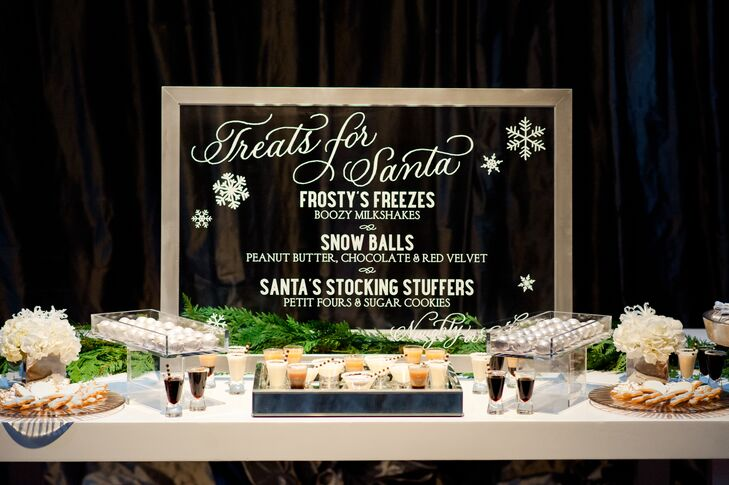 "Beneath a mirrored sign that read, ""treats for Santa"" were winter-themed sweets such as spiked milkshakes, snowball-themed cake balls and stocking stuffers including gift-wrapped petits fours and snowflake-shaped sugar cookies."