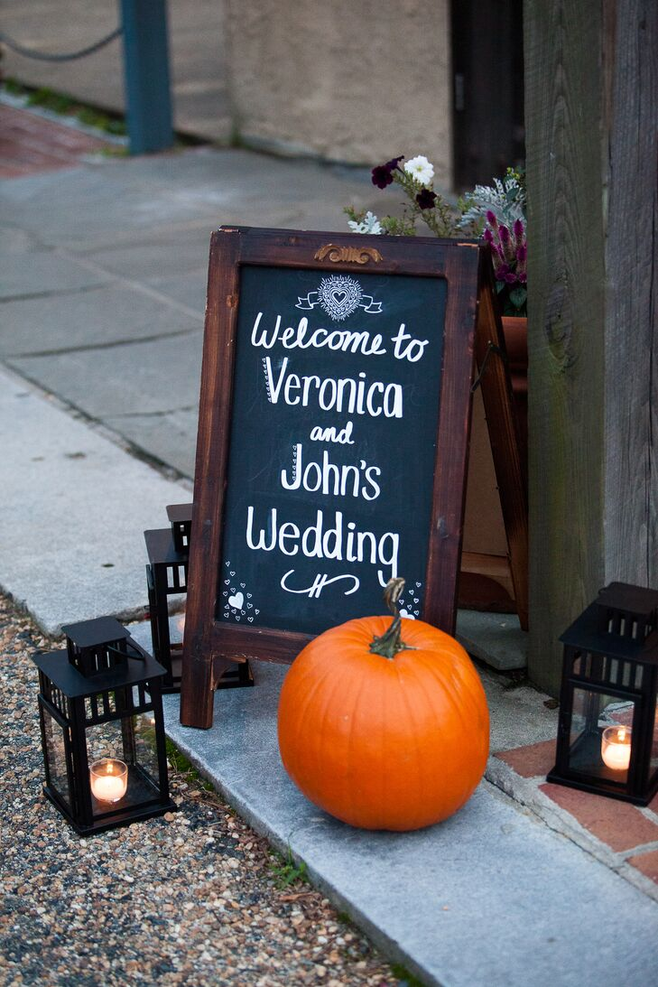 A sign welcoming guests to Veronica and John's wedding was positioned outside of the Williamsburg Winery, with a decorative pumpkin and lit candles.