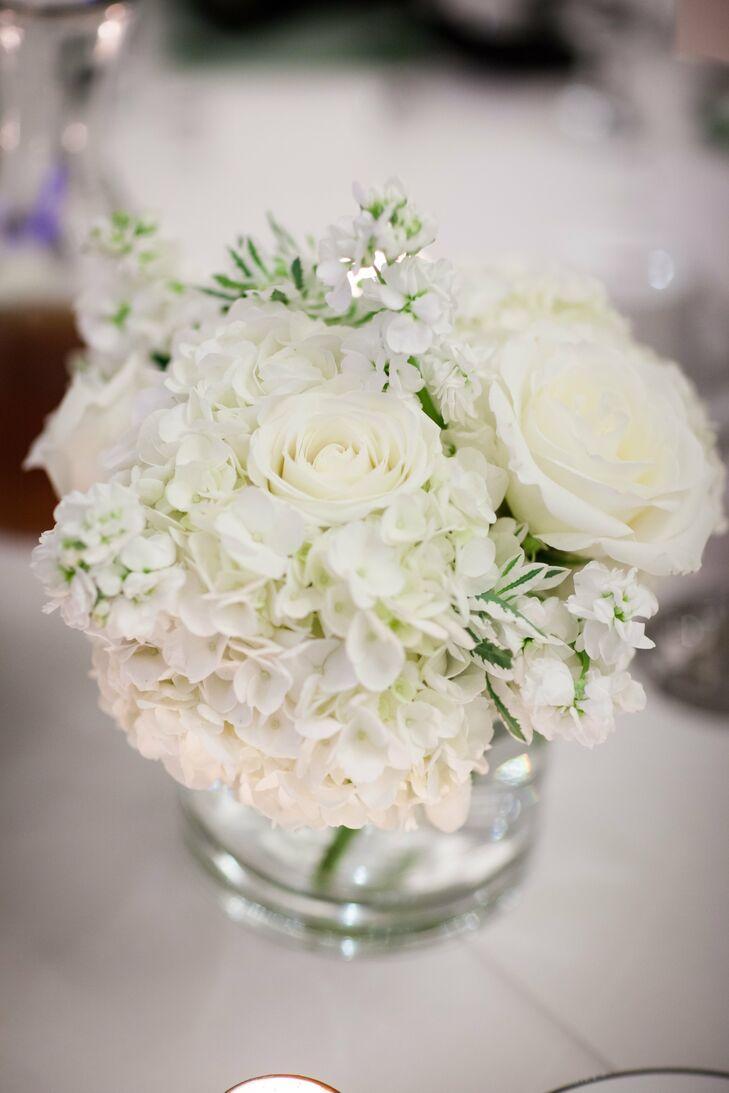 Small centerpieces filled with white roses, hydrangeas, ranunculuses and stock topped some of the guest tables at the reception.