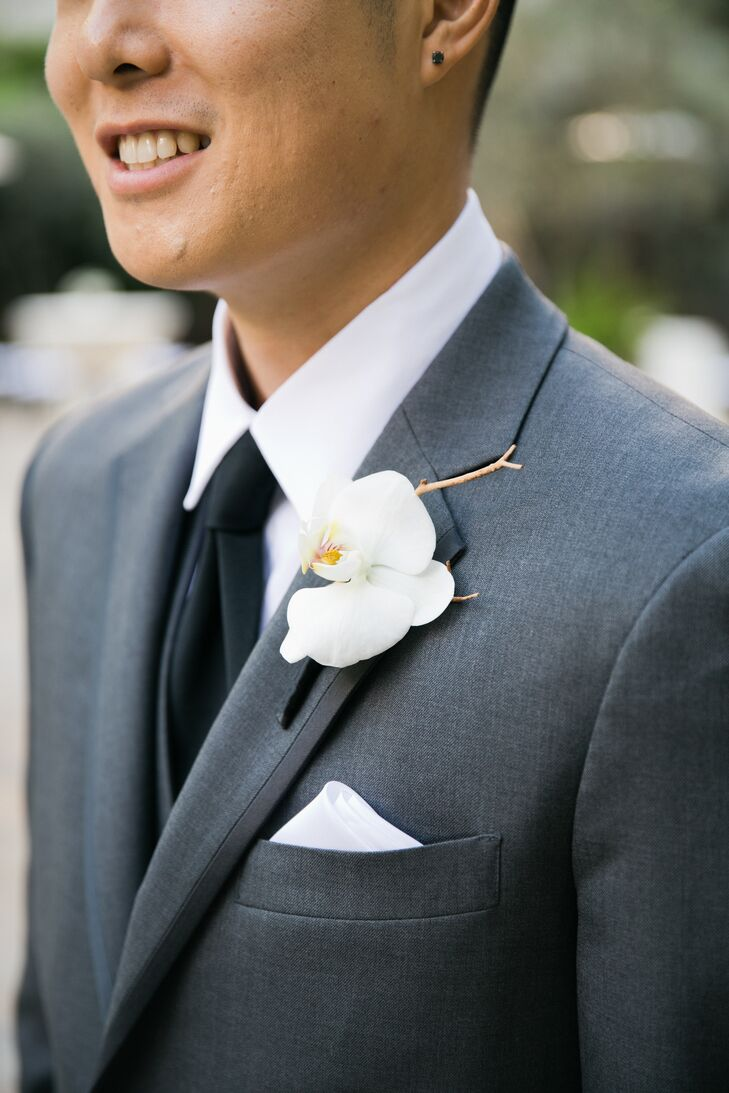 Ken had a single ivory orchid boutonniere pinned to his gray tuxedo lapel. The boutonniere matched Stephanie's bouquet well, which was an overflowing assortment of white orchids, both arranged by Lotus and Lily. Ken wore a white collared shirt with a classic black tie underneath his tuxedo jacket.