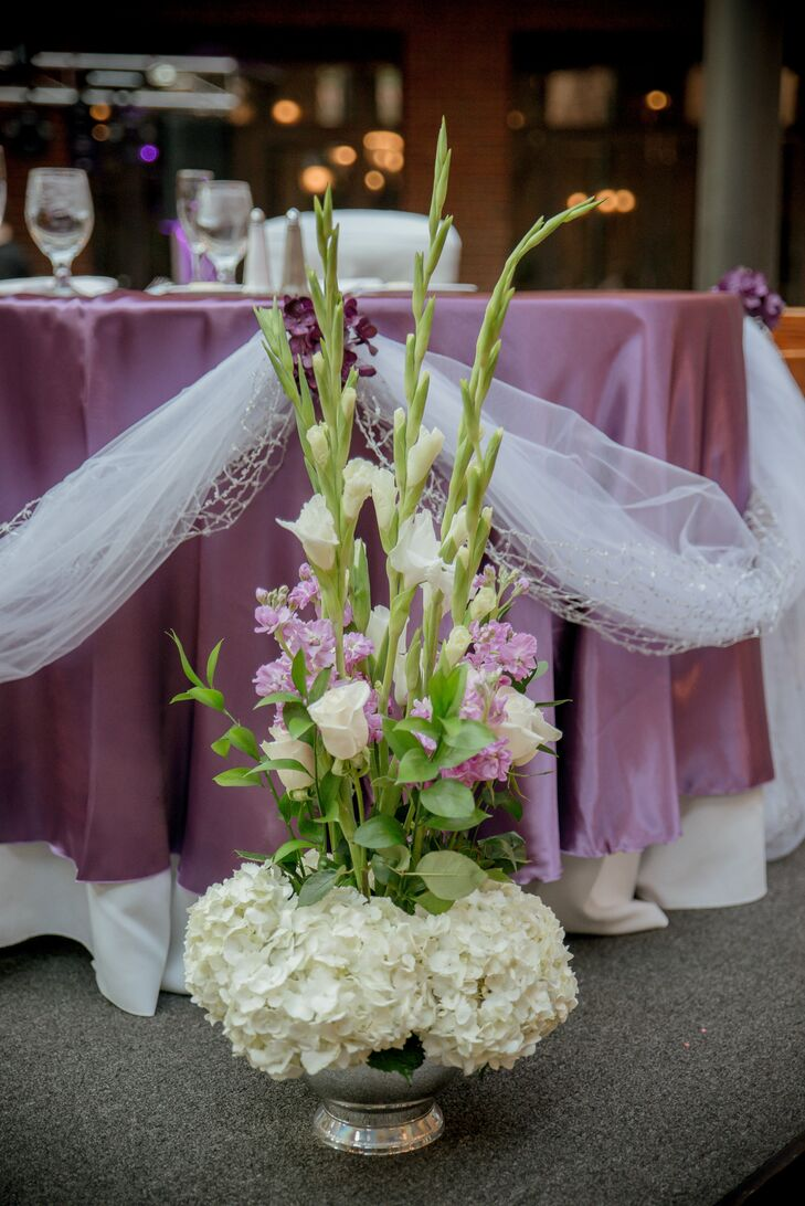 Beautiful Event Creations set up tables with purple linens and silver, satin chair covers for guests during the reception.