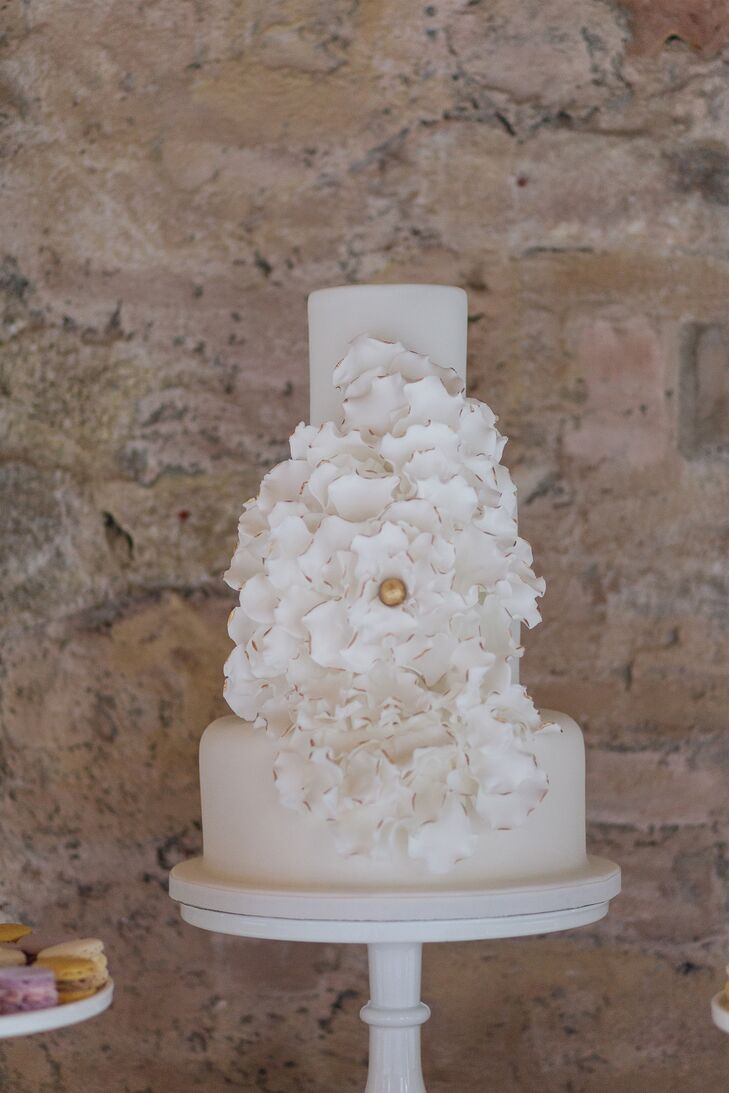 Elizabeth's penchant for modern design featured prominently in the couple's wedding cake. Three towering layers of white fondant-covered cake gave way to a textural fondant flower sculpted in the likeness of a hydrangea. Gold paint placed at the edges of the sugary creation added a hint of glamour and drama to the confection.
