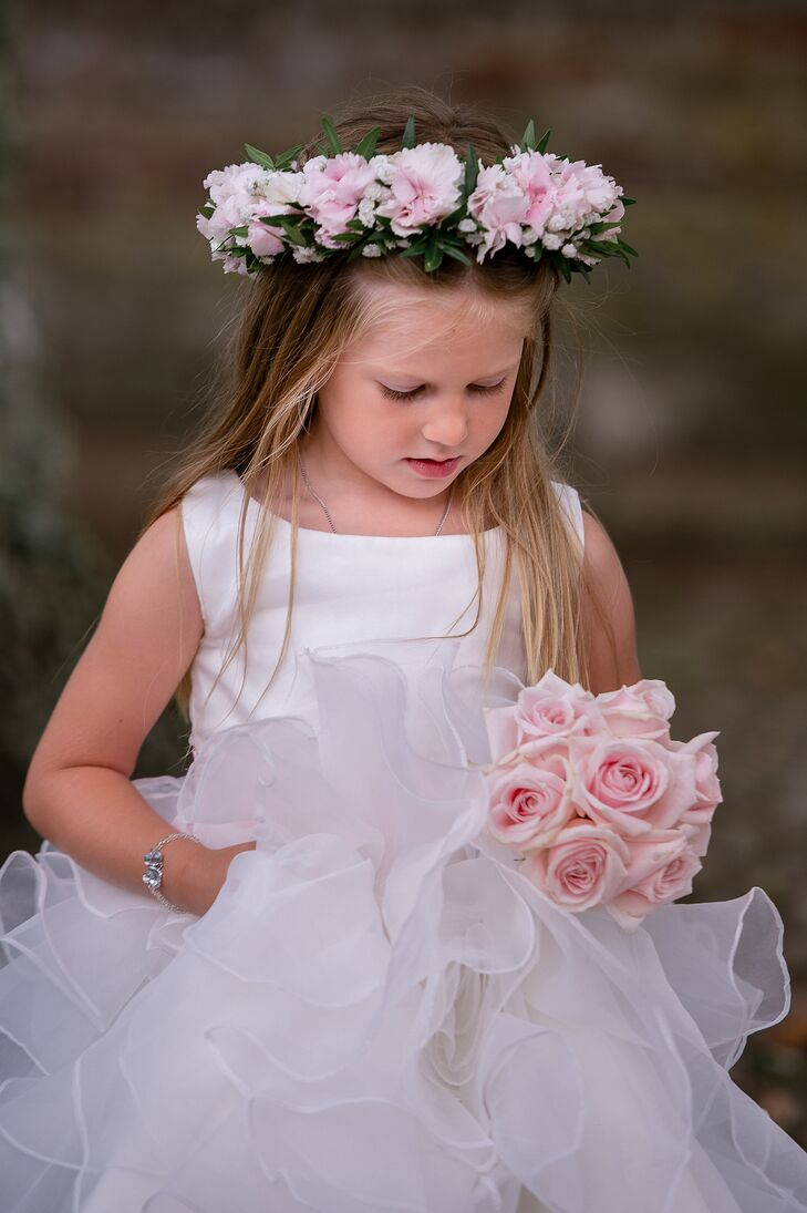 The couple's daughter wore a custom-made dress with a ruffled tulle skirt and a crown of blush flowers. She also carried a blush rose bouquet to match her mother's.