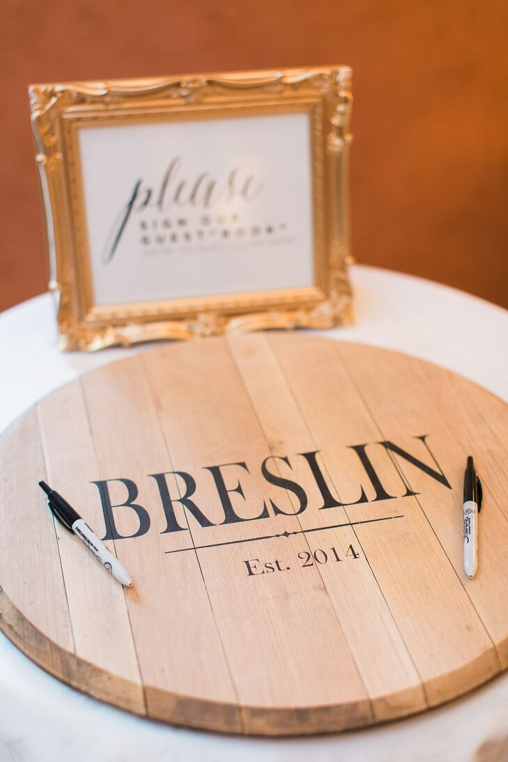 "Instead of pages or posters, Mariel and Colin asked guests to show their love on a custom, wooden board. Each person surrounded the couple's new last name, Breslin, and ""Est. 2014""  with well-wishes, advice and names in matching black text."