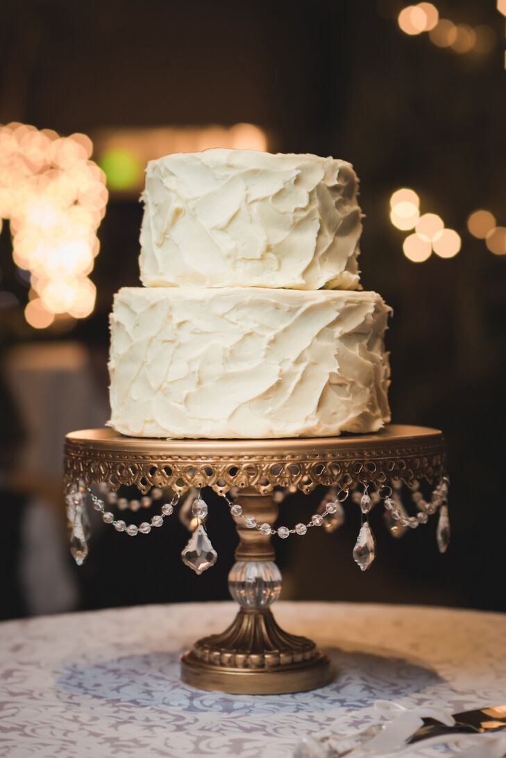 Heather and Ethen's wedding cake of two round tiers covered in textured buttercream rested on a vintage gold stand with dangling crystals to showcase the theme of simple elegance.
