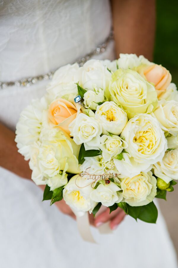 "Michelle held a gorgeous round bouquet filled with garden roses and spray roses in shades of peach and white. ""Inside my bouquet, we secured my 'something old,' a brooch from my nana (paternal grandmother), and my 'something blue,' which was a family ring from my husband's mother,"" Michelle says. ""The bouquet base was wrapped with my 'something borrowed,' fabric from my mother's wedding dress."""