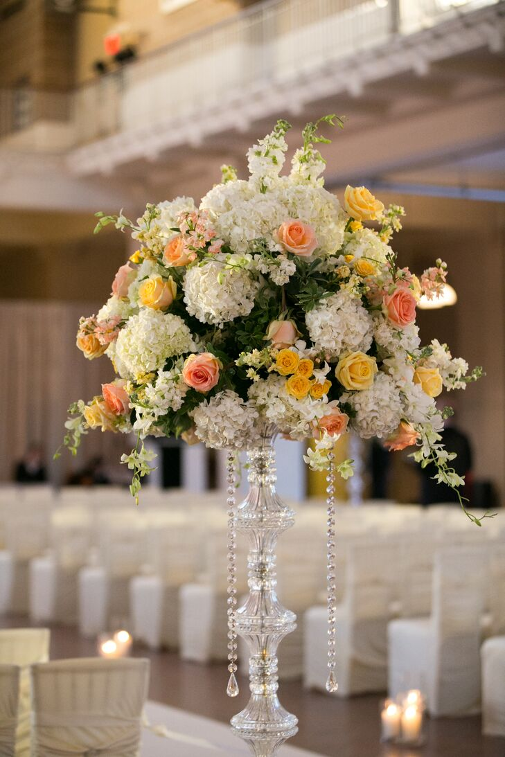 "While elegant and romantic, the ceremony decor was relatively traditional and understated, so it wouldn't overwhelm the beauty and grandeur of the historic space. Zak Events designed several lush, textured arrangements of white hydrangeas, peach roses and pink stock to sit atop tall crystal stands, which were placed at the entrance to and along the sides of the ceremony space. The floral arrangements played up the height of the room, while subtly adding to its striking features. ""All the beautiful architectural aesthetics aside, it was really all the history and stories living inside that room that made every moment of our wedding feel so extraordinary,"" Lauren says."