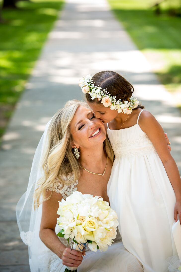 The flower girl wore a white A-line dress for the traditional wedding. She completed her look with a blush rose and white baby's breath flower crown for a little boho flair.