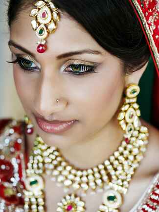 Indian bride wearing red with gold jewelry and gold eyeshadow