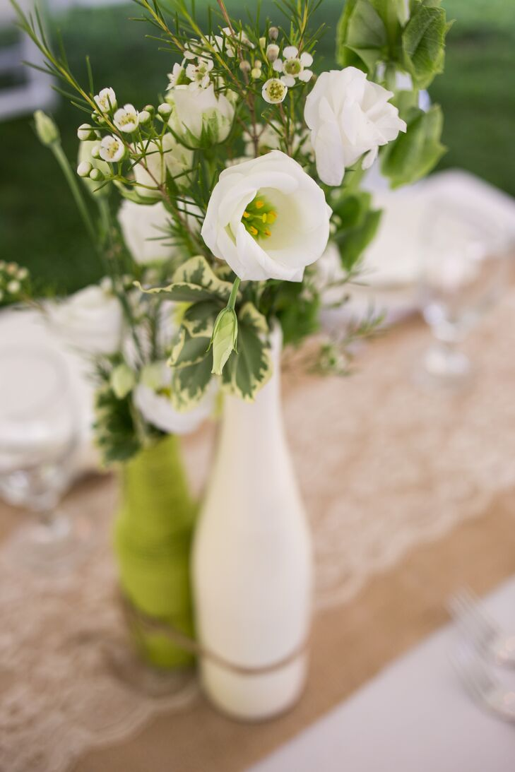 April's father spray painted bottles white and green to display the lovely white and green floral centerpieces at the tables.