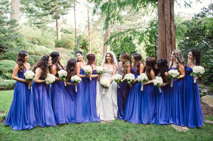 "Each of Tina's twelve bridesmaids wore a royal purple strapless dress from La Femme in their chosen style. ""I wanted them to wear dresses detailed enough to compliment my dress and the elaborate wedding theme,"" says Tina."