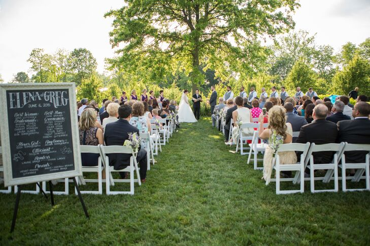 Elena and Greg got married under a tall tree at Jorgensen Farms in Westerville, Ohio, surrounded by the green natural landscaping that needed little additional decor. A chalkboard positioned at the front before entering the ceremony space listed the wedding party.