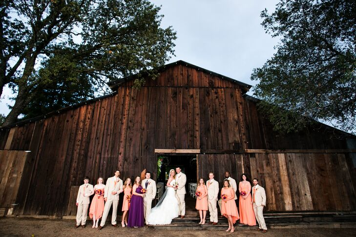 The couple and their wedding party stood in front of the rustic barn where the ceremony took place. Groomsmen matched the bridesmaids by wearing tangelo ties with their light tan suits.