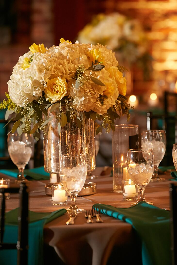 Mixed seasonal yellow and white flower arrangements filled mercury glass vases along and with candles in mercury glass votives.