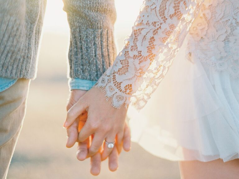 Newly engaged couple holding hands
