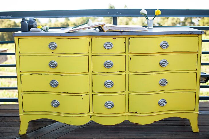 A bright-yellow vintage dresser displayed the guest book at the wedding.
