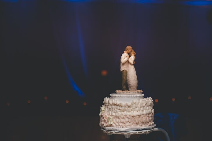 The blush and ivory iced cake was filled with raspberry filling, and had a cake topper that depicted a man and a woman embracing one another.