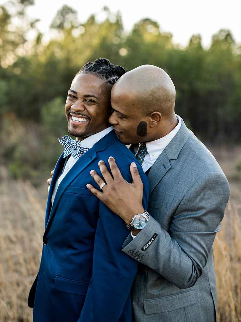 Grooms hugging in a field